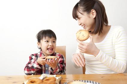 クッキーを食べる女の子と女性