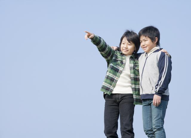 遠くを眺める小学生の男の子2人