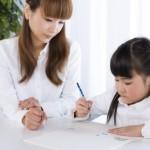 母親に勉強を教わる女の子