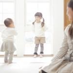 遊ぶ子供達を見つめる母親